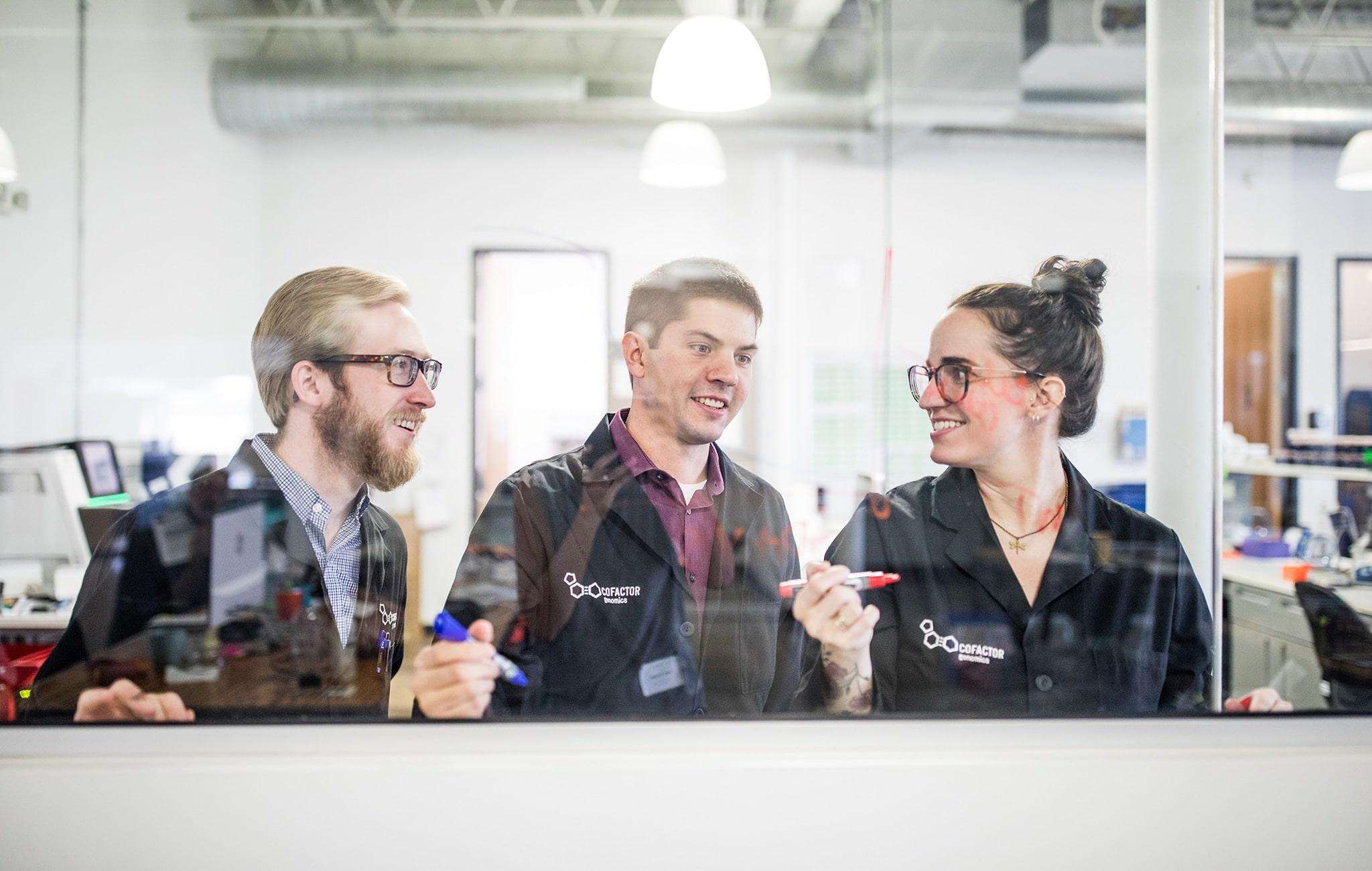 Three people behind glass